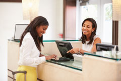 Kvinna som in kontrollerar på hotellmottagandet som använder den Digital minnestavlan Royaltyfri Fotografi