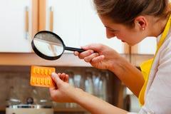 Kvinna som kontrollerar preventivpillerar med förstoringsglaset Arkivfoto