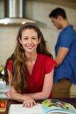 Kvinna som kontrollerar receptbok- och manmatlagningen på ugnen Fotografering för Bildbyråer