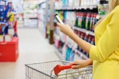 Kvinna som kontrollerar shoppinglistan på hennes smartphone Arkivfoto