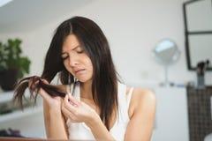 Kvinna som kontrollerar slutet av hennes hår för kluvna hårtoppar Arkivfoto