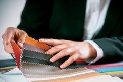 Kvinna som kontrollerar tygfärgprovkartor Royaltyfri Bild