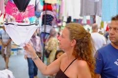 Kvinna som kontrollerar underkläderna i utomhus- marknad Arkivbild
