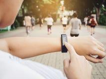 Kvinna som kontrollerar utrustning för sport för klocka för genomkörare för övning för hjärtahastighet utomhus- smart fotografering för bildbyråer