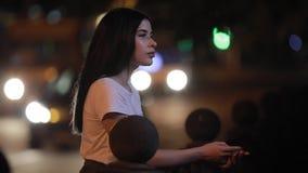 Kvinna som kopplar av anseende nära staketet på natten arkivfilmer