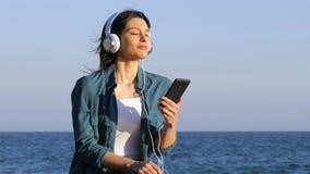 Kvinna som kopplar av att lyssna till musik på stranden