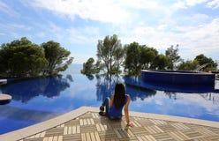 Kvinna som kopplar av bredvid en storslagen simbassäng Arkivbild