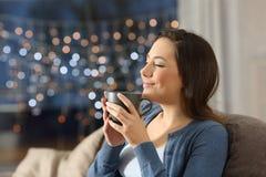 Kvinna som kopplar av dricka kaffe i natten hemma royaltyfria foton