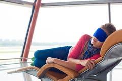 Kvinna som kopplar av i ögonsömnmaskering på flygplatsen Fotografering för Bildbyråer