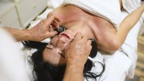 Kvinna som kopplar av i brunnsortsalong med varma stenar stock video
