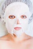 Kvinna som kopplar av i brunnsortsalongen som applicerar den vita framsidamaskeringen Royaltyfri Fotografi