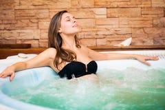 Kvinna som kopplar av i en bubbelpool Arkivbild