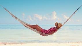 Kvinna som kopplar av i en hängmatta på den tropiska östranden Exotisk semester för sommar stock video