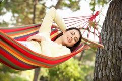Kvinna som kopplar av i hängmatta Royaltyfri Foto