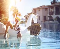 kvinna som kopplar av i lyxigt simbassängsemesterorthotell på den stora uppblåsbara enhörningen som svävar den pegasus flötet arkivbild