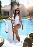 kvinna som kopplar av i lyxigt simbassängsemesterorthotell på den stora uppblåsbara enhörningen som svävar den pegasus flötet arkivbilder
