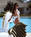 kvinna som kopplar av i lyxigt simbassängsemesterorthotell på den stora uppblåsbara enhörningen som svävar den pegasus flötet royaltyfria bilder