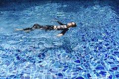 Kvinna som kopplar av i pölen, flicka i swimwear som svävar i det klara dammet royaltyfria foton