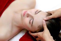 Kvinna som kopplar av i skönhetbehandlingen, ansikts- massage Arkivbild