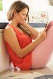Kvinna som kopplar av med den hemmastadda tidningen Arkivfoto
