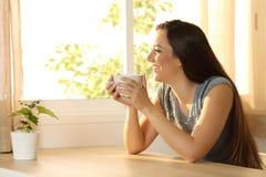 Kvinna som kopplar av med en kaffekopp Arkivfoto