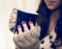 Kvinna som kopplar av och rymmer en kopp kaffe eller ett te Royaltyfri Fotografi