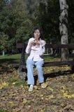 Kvinna som kopplar av på bänken i höst Arkivfoton