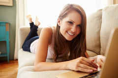 Kvinna som kopplar av på den Sofa At Home Using Laptop datoren arkivbild