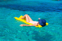 Kvinna som kopplar av på den uppblåsbara madrassen i havet Arkivbild