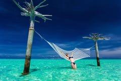 Kvinna som kopplar av på denvatten hängmattan i mitt av tropiskt l arkivbild