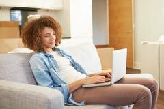 Kvinna som kopplar av på det Sofa With Laptop In New hemmet Arkivfoton
