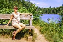 Kvinna som kopplar av på en bänk Fotografering för Bildbyråer