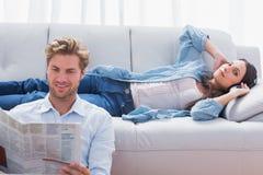 Kvinna som kopplar av på en soffa som lyssnar till musik arkivbilder
