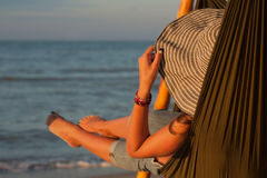 Kvinna som kopplar av på hängmattan med hatten som solbadar på semester Mot bakgrunden av havet i inställningssolen Arkivbild