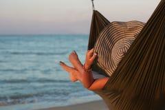 Kvinna som kopplar av på hängmattan med hatten som solbadar på semester Mot bakgrunden av havet i inställningssolen Arkivbilder