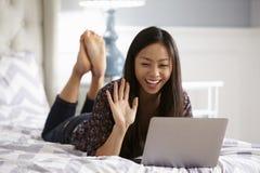 Kvinna som kopplar av på säng genom att använda bärbar datordatoren för den videopd appellen royaltyfri fotografi