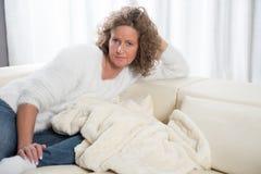 Kvinna som kopplar av på soffan Royaltyfria Bilder
