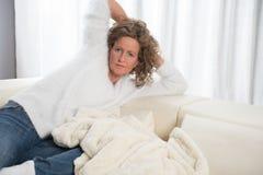 Kvinna som kopplar av på soffan Arkivbild