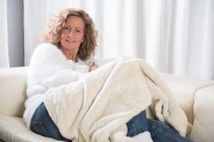Kvinna som kopplar av på soffan Royaltyfri Bild