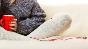 Kvinna som kopplar av på soffan med smartphonen arkivbild