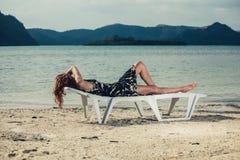 Kvinna som kopplar av på sunbed i vändkretsarna Royaltyfri Foto