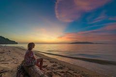 Kvinna som kopplar av p? romantisk himmel f?r sandstrand p? solnedg?ngen, bakre sikt, guld- cloudscape, verkligt folk Indonesien  fotografering för bildbyråer