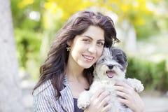 Kvinna som kramar hennes utomhus- lilla hund Arkivbilder