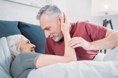 Kvinna som kramar maken, medan vila i säng tillsammans Arkivbilder