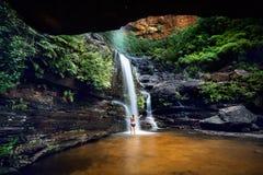 Kvinna som kyler av i en bergoas och vattenfall arkivbild