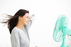 Kvinna som kyler sig vid den elektriska fanen Royaltyfri Foto