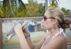 Kvinna som kysser en havssköldpadda Arkivbild