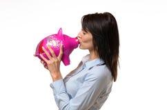 Kvinna som kysser en spargris i henne händer fotografering för bildbyråer