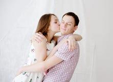 Kvinna som kysser hennes pojkvän i kind Arkivfoton