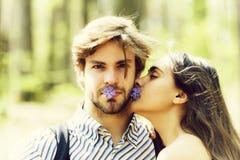 Kvinna som kysser mannen på naturlig bakgrund royaltyfri foto